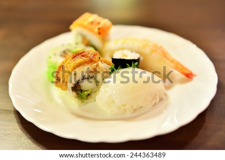 Very shallow DOF image of a white plate with fresh sushi - stock photo