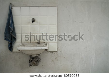 very simple old washbasin over a  white grunge wall - stock photo