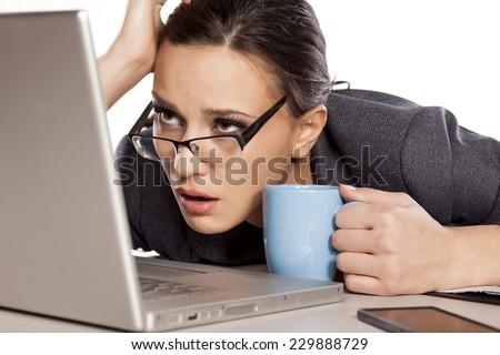 very sleepy and tired business woman on laptop, holding a coffee mug - stock photo