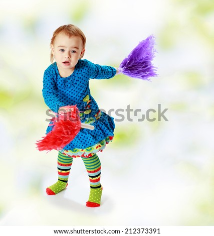 very small and very cheerful girl waving colored toys.the concept of a happy childhood, education of children, teens - stock photo