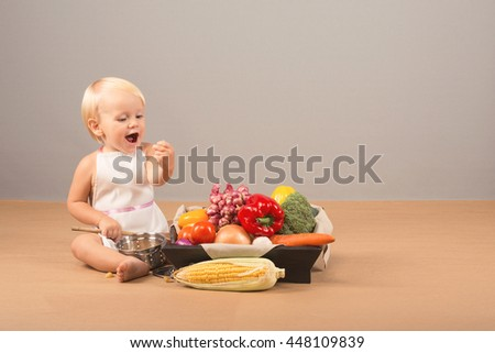 Very small, charming child with a happy vegetarian eats vegetables: corn, peppers, broccoli, onions, carrots - stock photo