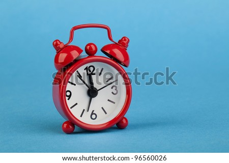 Very small Red alarm clock on the blue background.
