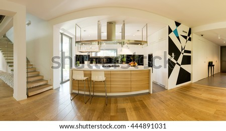 Very spacious ground floor of a contemporary house with a kitchen space and a kitchen island - stock photo