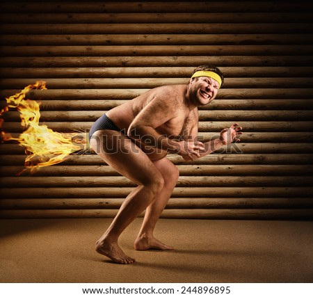 Very strange naked man farts by fire - stock photo