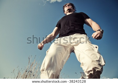 Very strong and angry man. View from below. - stock photo