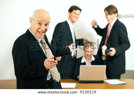very successful business team with a portrait of the team leader in foreground (selective focus only on the team leader!) - stock photo