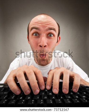 Very surprised funny nerd working on computer - stock photo