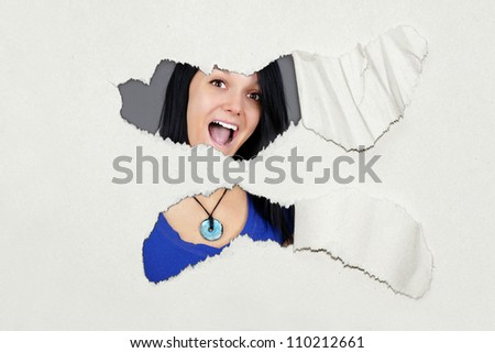 Very surprised young woman under ripped thick textured paper, fun advertisement. - stock photo