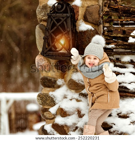 Very sweet beautiful little girl child in a beige coat crusade amid rustic winter near the lantern, square format - stock photo
