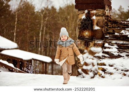 Very sweet beautiful little girl child in a beige coat smiles and runs on the background of the winter village near the lantern - stock photo