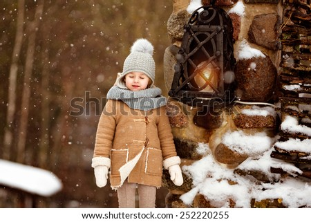 Very sweet beautiful little girl child in a beige coat turned a blind eye to the background of the winter village near the lantern - stock photo