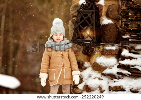 Very sweet beautiful little girl child in the beige coat is on the background of the winter village near the lantern - stock photo