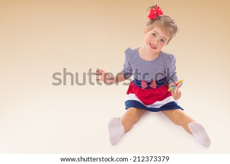 Very sweet little girl sitting on the floor.the concept of a happy childhood, education of children, teens - stock photo