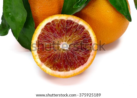 Very tasty and juicy, freshly picked MORO RED Blood Oranges from Sicily with natural leaves, sliced, cultivated with organic method of farming, guaranteed without pesticide. isolated on white