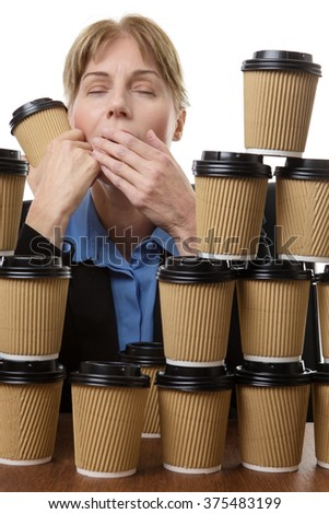 Very tired business woman is yawning whilst hiding behind many disposable cups. Studio shot isolated on white - stock photo