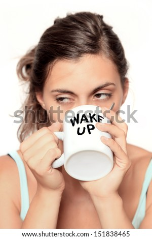 "very tired looking woman early in the morning drinking a cup of coffee to ""wake up"" - selective focus on cup - isolated on white  - stock photo"