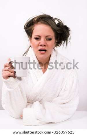 very tired young woman holding a coffee cup and wearing a bathrobe - stock photo