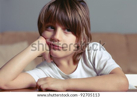 Very unhappy boy sits at the desk and looks away - stock photo