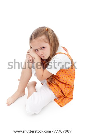 Very upset little girl sitting on the floor about to cry - stock photo