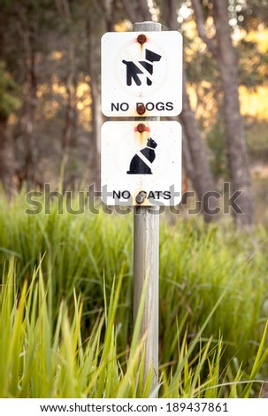 Very weathered and faded sign in Australian environmental conservation area stating NO DOGS, NO CATS to preserve native animal habitat - stock photo
