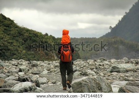 Very young asian boy carried by his father on his shoulders heading to Franz Josef Glacier in New Zealand - stock photo