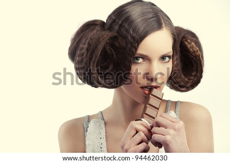 very young pretty girl with creative hairstyle eating a tablet of chocolate wearing a old style dress - stock photo