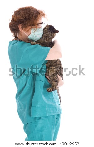 Vet in green uniform, medical mask and protective glasses  hugging Cat In Surgery - stock photo