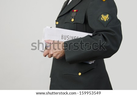 Veteran holding newspaper with business section/Veteran Looking for Work/Veteran in an army uniform holding business pages - stock photo