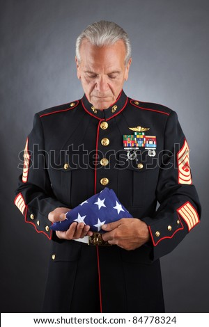 Veteran Soldier Marine holds a Flag - stock photo