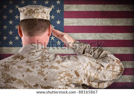 VETERAN SOLDIER | Marine in Desert Fatigues Saluting an American Flag - stock photo