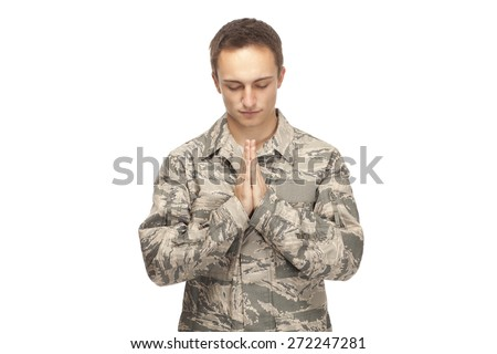 VETERAN SOLDIER PRAYING   MILITARY CHURCH   ARMED FORCES RELIGION AND PRAYER   Air force airman with hands clasped in prayer against white background - stock photo