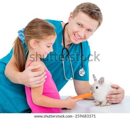 veterenarii and a pretty  little girl feeding rabbit carrot - stock photo
