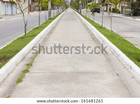 Via - cement sidewalk - woman walking in the background - small town - stock photo
