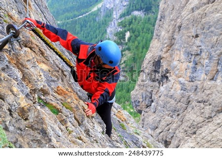 "Via ferrata ""Brigata Tridentina"" with steep walls and woman climber high above distant ground, Sella massif, Dolomite Alps, Italy - stock photo"