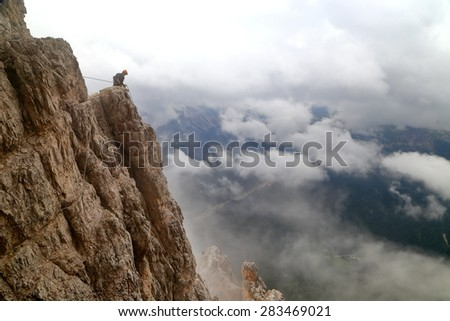 Via ferrata climber ascending a cliff above the clouds, Tofana massif, Dolomite Alps, Italy