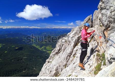 "Via ferrata climber clipping gear to steel cable of ""Passo Santner"" route, Catinaccio massif, Dolomite Alps, Italy - stock photo"