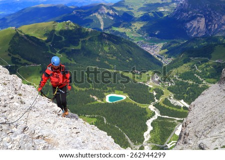 Via ferrata climber high above valley and distant town of Val Gardena, Dolomite Alps, Italy