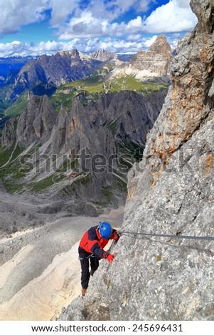 "Via ferrata climber traversing high above ground along steel cable of ""Merlone"" route, Cadini di Misurina, Dolomite Alps, Italy - stock photo"