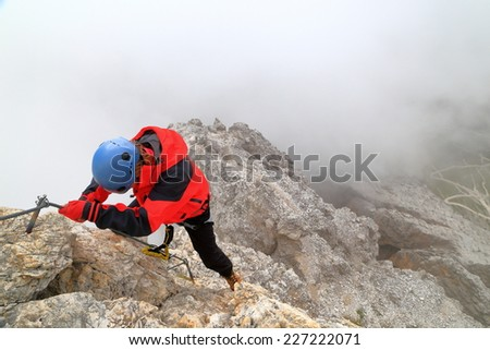 "Via ferrata ""Punta Ana"" with woman climber ascending a steep ridge in harsh weather, Tofana massif, Dolomite Alps, Italy - stock photo"