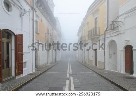Via Garibaldi in fog, Monte Sant'Angelo - stock photo