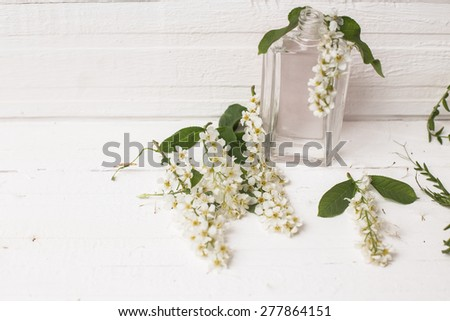 vial and a bouquet of flowers on a white wooden table