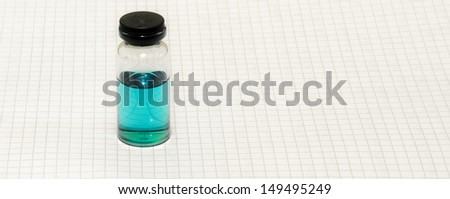 Vial of blue liquid on graph paper - stock photo