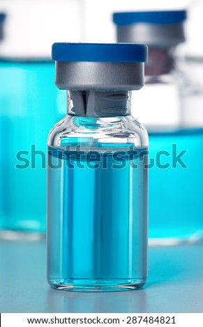 Vials of the vaccine, blue background - stock photo