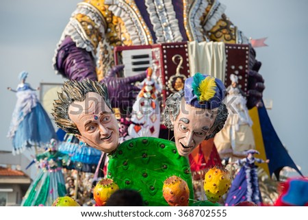 VIAREGGIO, ITALY - FEBRUARY 17, 2013 - Carnival Show parade on town street with traditional Burlamacco Pulcinella style mask and wagon papier mache stone faced parade - stock photo