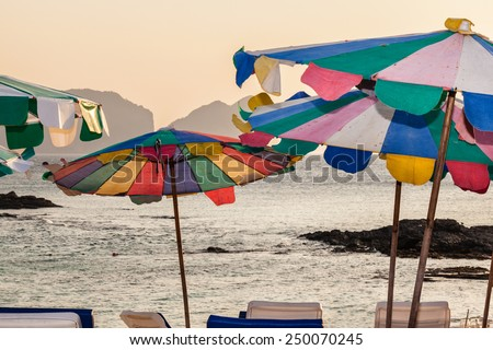 vibrant and multi colored beach umbrellas in a tropical paradise - stock photo