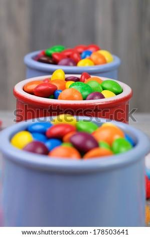 Vibrant candies in three  ceramic jars - stock photo