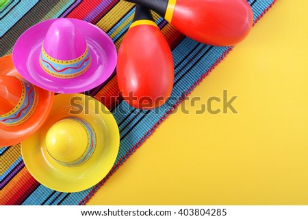 Vibrant Cinco de Mayo background with sombrero hats and maracas on bright festive background, with copy space.  - stock photo