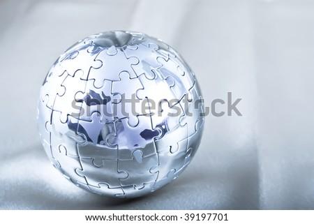 Vibrant Color Metal Puzzle Globe On Satin - stock photo