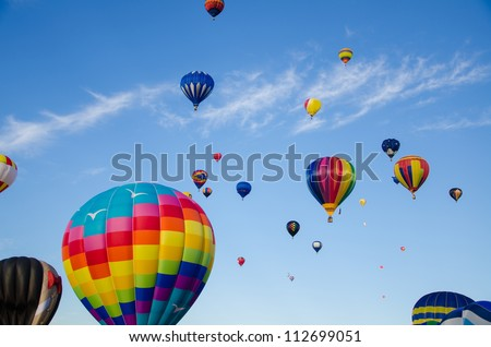 Vibrant, colorful, Hot air balloons float up into the sky. - stock photo