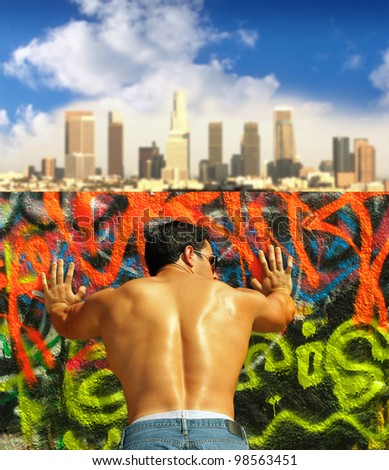 Vibrant colorful outdoor portrait of a very muscular young man leaning against graffiti covered wall with city skyline in the background taken from behind - stock photo